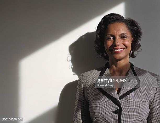 Mujer madura contra la pared, sonriendo, retrato