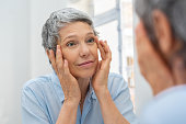 Beautiful senior woman checking her face skin and looking for blemishes. Portrait of mature woman massaging her face while checking wrinkled eyes in the mirror. Wrinkled lady with grey hair checking w