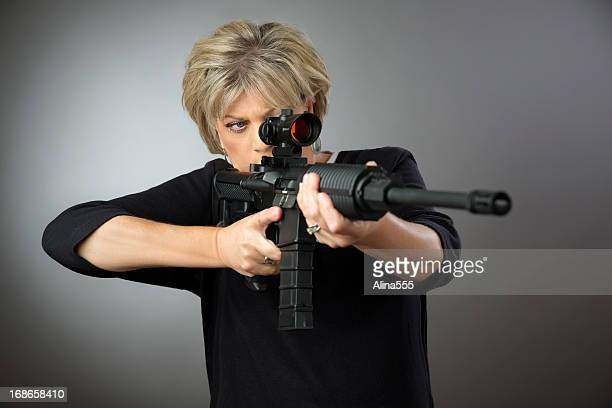 Mature woman aming a rifle on gray background