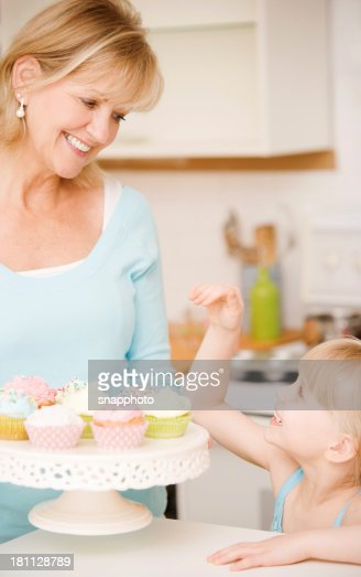 Woman Decorating Cupcakes mature woman and child eating cupcakes stock photo | getty images