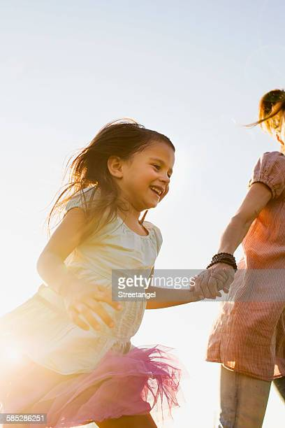 Mature woman and daughter holding hands and running in park
