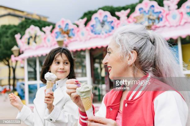 Mature woman and girl eating ice cream cones outside ice cream parlour, Florence, Italy