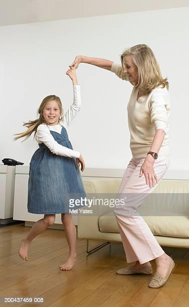 Mature woman and granddaughter (8-10) dancing, indoors