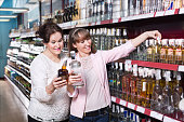Ordinary mature woman and her adult daughter buying strong alcohol