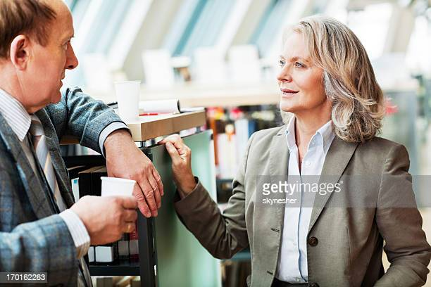 Mature woman and man talking in a library.