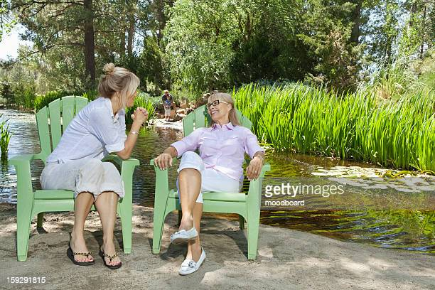 Mature woman and mother relaxing with man and child fishing in the background