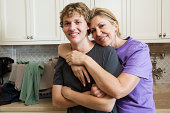 Mature woman and son in laundry room, portrait