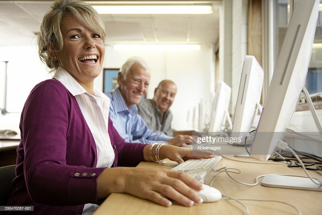 'Mature woman and two mature men in computing class, portrait' : Stock Photo