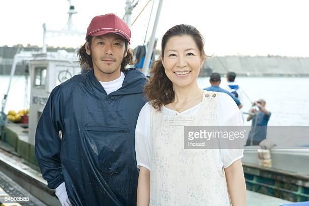 Mature woman and young fisherman smiling on port