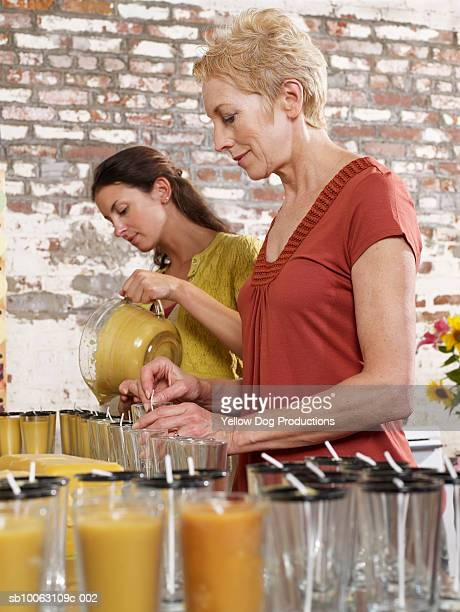 Mature woman and young woman making candles, low angle view