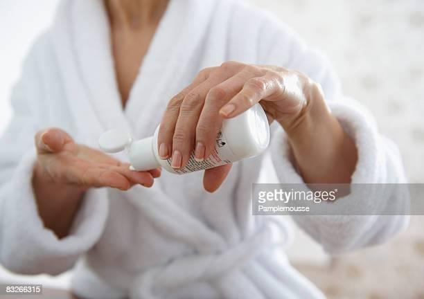 Mature woman applying moisturizer