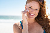 Smiling young woman applying sunscreen lotion on face at beach, with copy space. Beautiful mature woman with red hair enjoying summer at sea. Portrait of happy girl using sunblock on her delicate skin