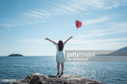 Mature woman arms outstretched with heart shaped balloon