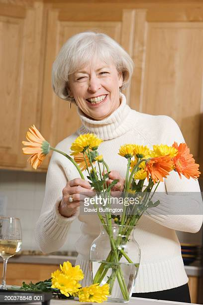 Mature woman arranging flowers in vase in kitchen, smiling, portrait