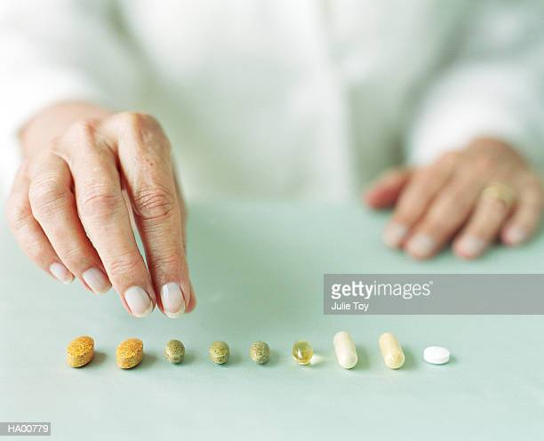 Mature woman arranging pills in row