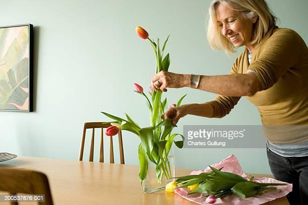 Mature woman arranging tulips in vase, smiling