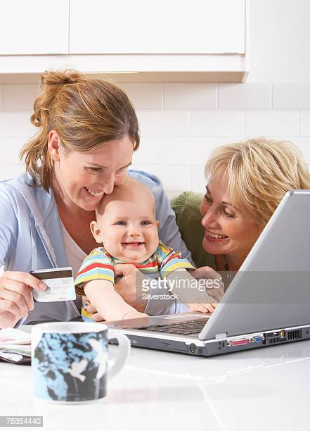 Mature woman assisting adult daughter with son (3-6 months) using laptop in kitchen