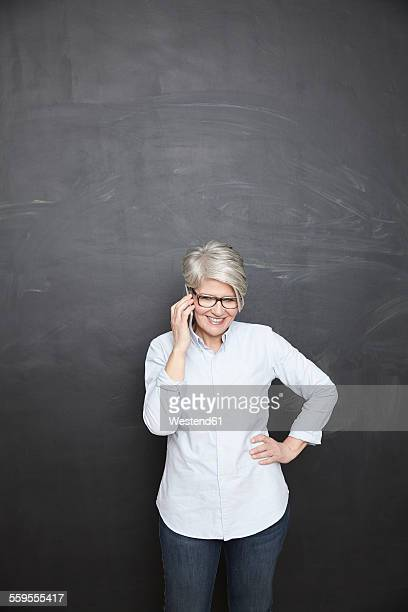 Mature woman at blackboard on cell phone