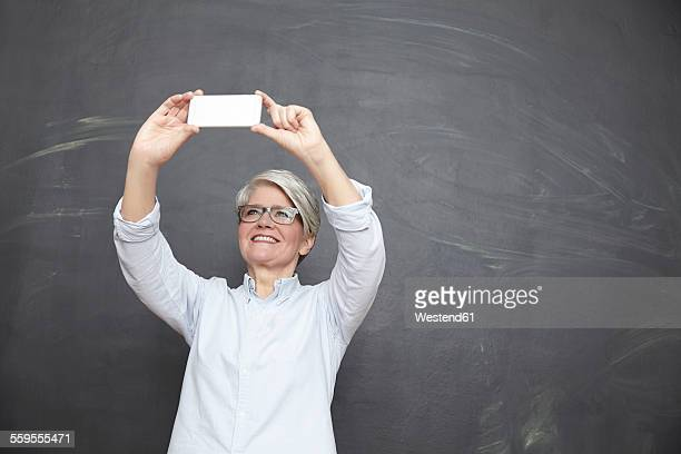 Mature woman at blackboard taking selfie