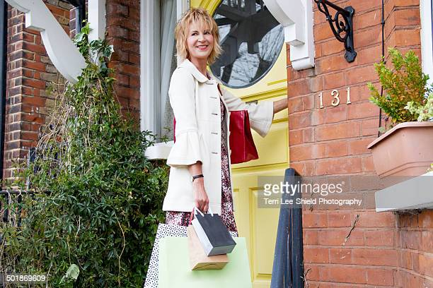 Mature woman at front door with shopping bags