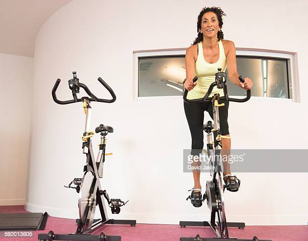 Mature woman at gym on exercise bicycle