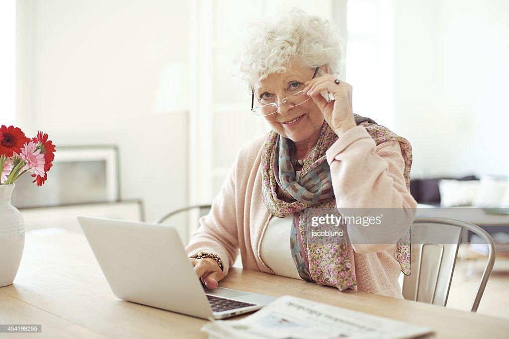 Mulher Madura em casa utilizando o computador portátil : Foto de stock