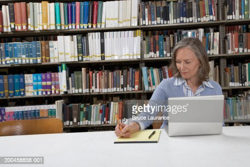 Mature woman at library table, using laptop and writing notes : Stock-Foto