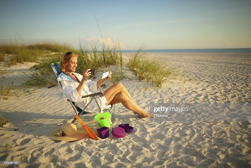 Mature woman at the beach depositing a check with phone