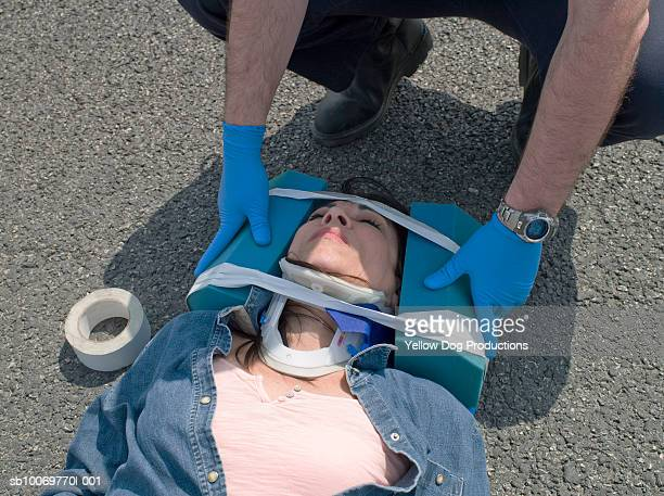 Mature woman being put in neck brace after accident