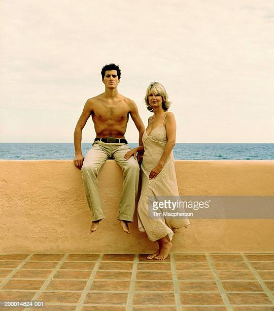 Mature woman beside young man sitting on wall, portrait