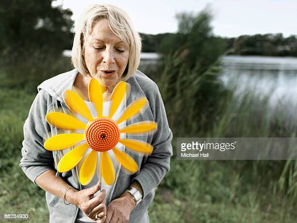 Mature woman blowing wind flower