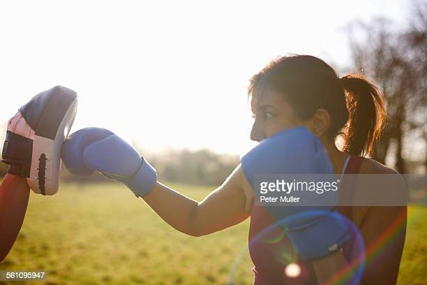Mature woman boxer training in field