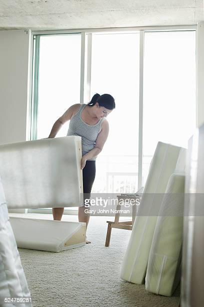Mature woman building flatpack furniture.