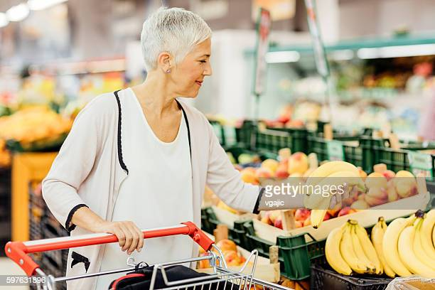 Mature Woman Buying Fruits In Local Supermarket.