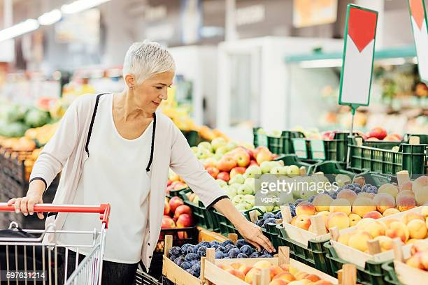 Mature Woman Buying Organic Fruits In Local Supermarket.