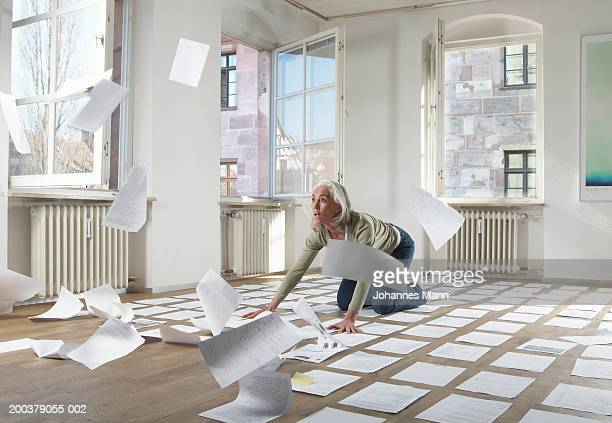 Mature woman by papers blowing in wind indoors