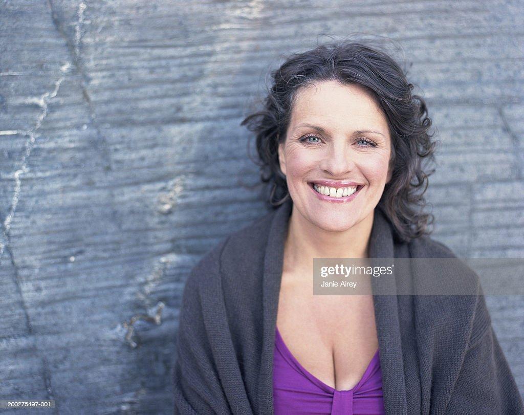 Mature woman by rock, smiling, portrait, close-up