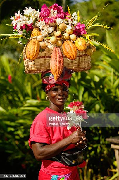Mature woman carrying basket of fruit on head, smiling, portrait