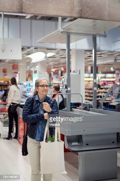 Mature woman carrying shopping bag while walking against checkout counter at supermarket