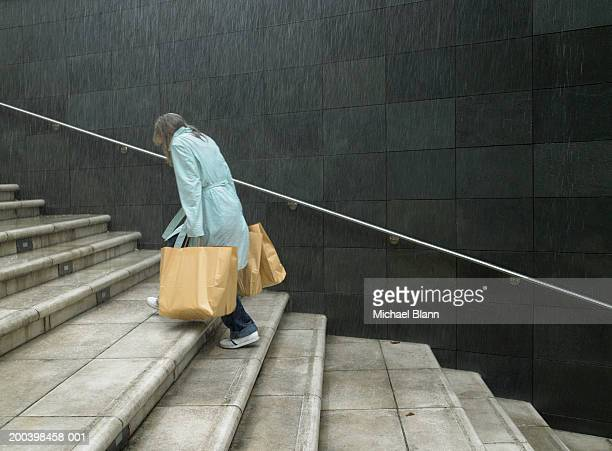 Mature woman carrying shopping bags up steps in rain, side view