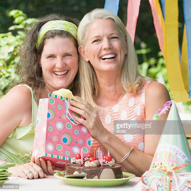 Mature woman celebrating her birthday with her friend