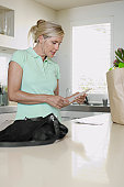 Mature woman checking receipts in kitchen