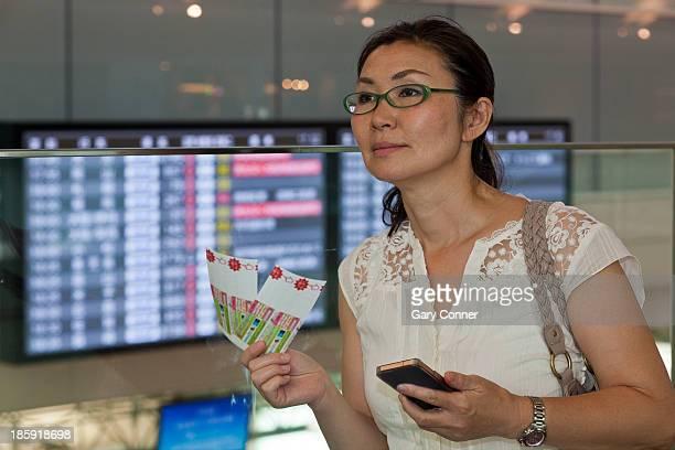 Mature woman checks air plane ticket