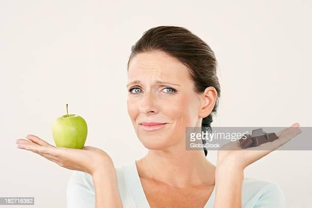 Mature woman choosing between apple and chocolate