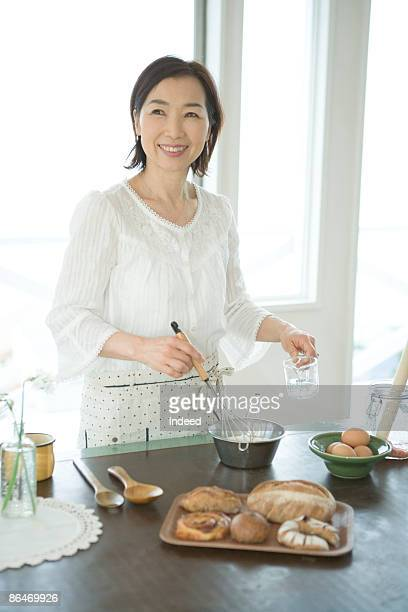 Mature woman cooking, looking away