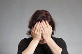 Mature woman covering eyes