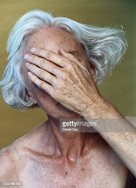 Mature woman covering face with hand, close-up