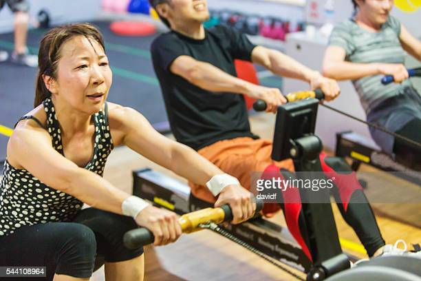 Mature Woman Cross Training Athlete Workout With Rowing Machine Exercise
