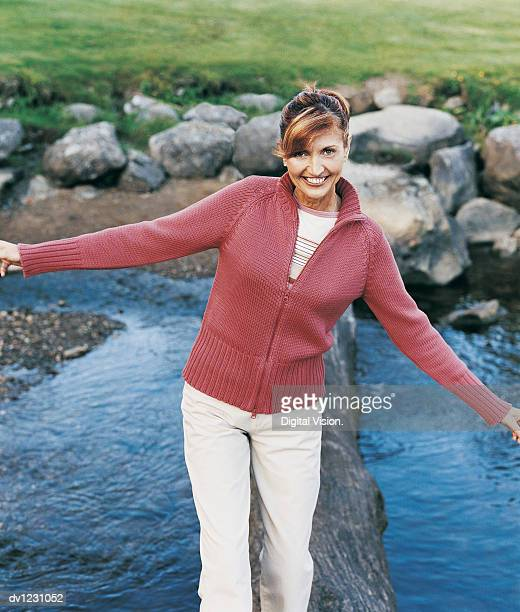 Mature Woman Crossing a River Walking on a Treetrunk