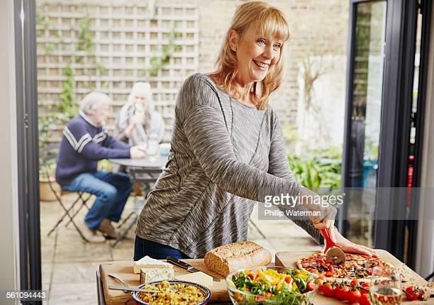 Mature woman cutting pizza